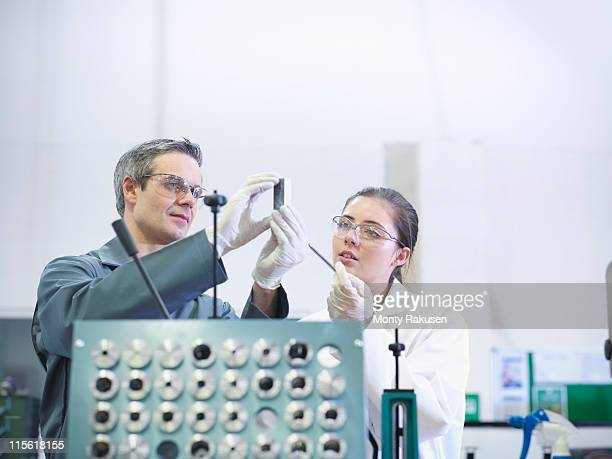 Male engineer and female scientist inspect an engineering part in a factory