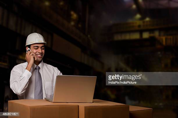 Male engineer answering mobile phone while using laptop on cardboard boxes