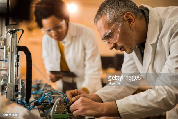 Male engineer assembling wires on production line component.
