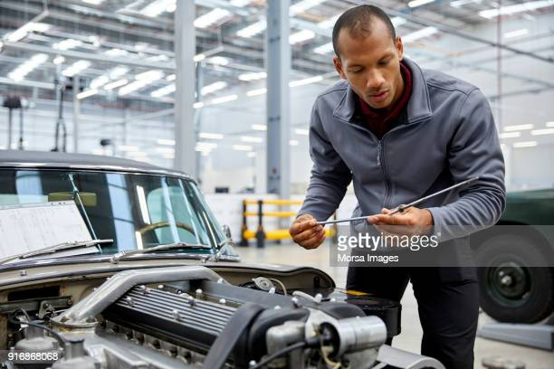 Male engineer checking oil with dipstick by car