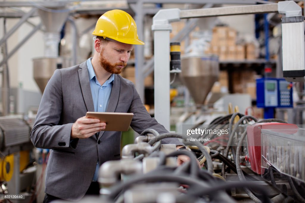Male engineer checking pressure in machines in factory : Stock Photo