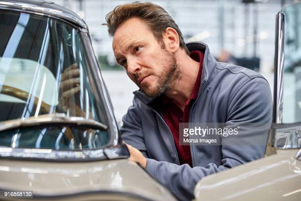 male engineer examining vintage car in industry - vintage car stock pictures, royalty-free photos & images