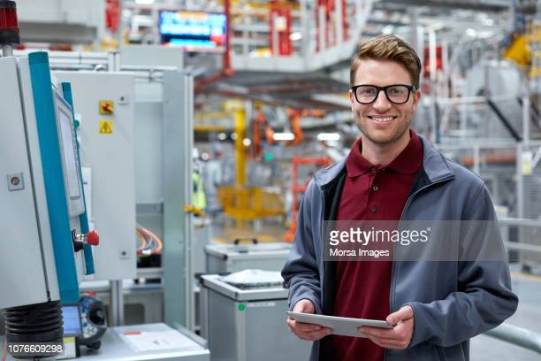male engineer holding tablet pc at car plant - engineering stock pictures, royalty-free photos & images