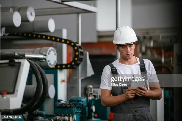 männliche ingenieur in der fabrik mit tablet - serbien stock-fotos und bilder