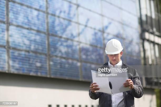 male engineer looking at paperwork on solar panel site - sigrid gombert stock-fotos und bilder