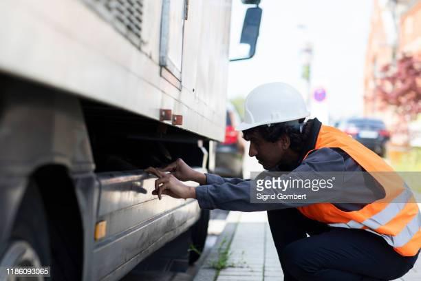 male engineer looking beneath truck - sigrid gombert stock-fotos und bilder