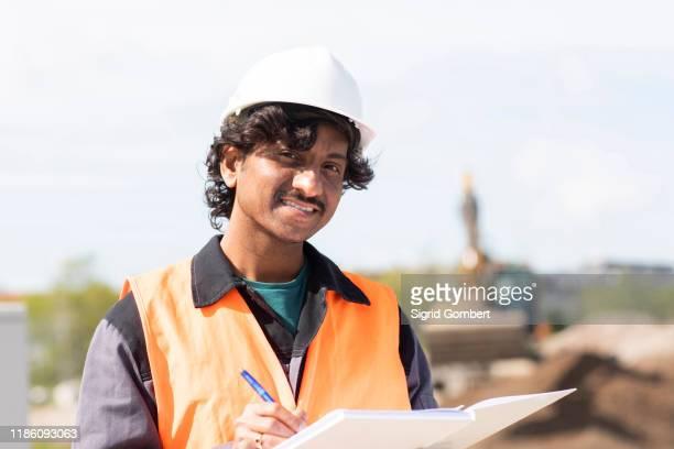male engineer on construction site writing in notebook, head and shoulder portrait - sigrid gombert stock-fotos und bilder