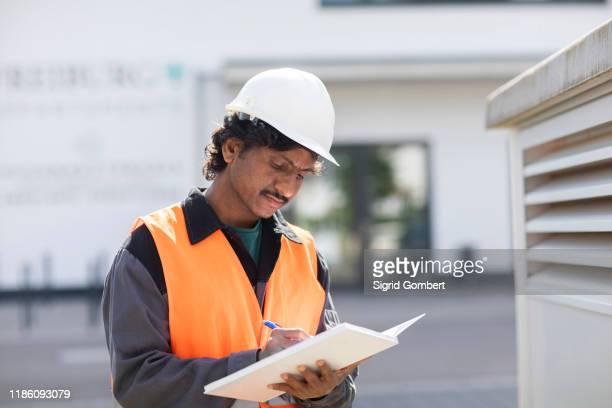 male engineer outside industrial building writing in notebook - sigrid gombert stock-fotos und bilder