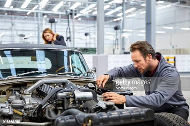 male engineer repairing vintage car in industry - vintage auto repair stock pictures, royalty-free photos & images