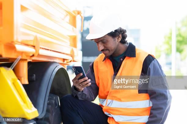 male engineer standing next to yellow truck looking at smartphone - sigrid gombert stock-fotos und bilder
