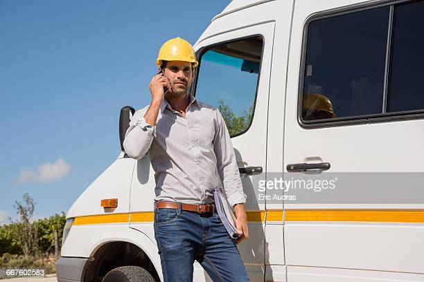 Male engineer talking on a mobile phone by van at site