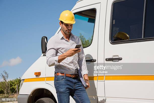 Male engineer using a mobile phone by van at site