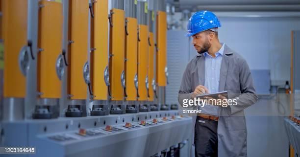 engenheiro masculino usando tablet digital na fábrica - só um homem jovem - fotografias e filmes do acervo