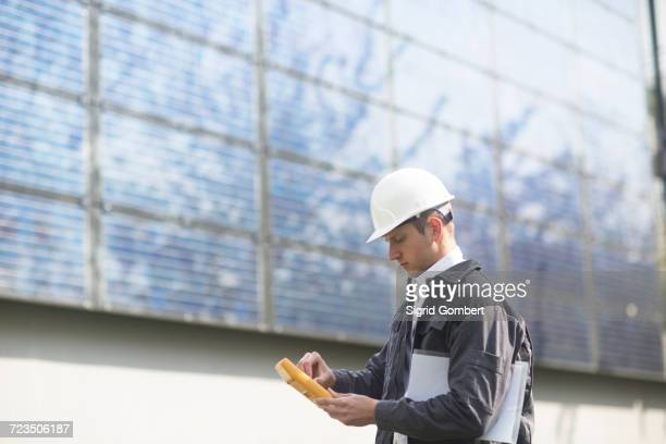 male engineer using multimeter on solar panel site - sigrid gombert - fotografias e filmes do acervo