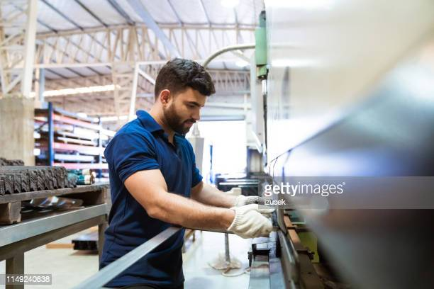 male engineer using puller machine in factory - making stock pictures, royalty-free photos & images