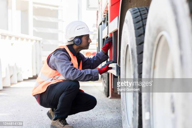 male engineer wearing hardhat and ear protectors checking undercarriage of a lorry. - sigrid gombert stock pictures, royalty-free photos & images