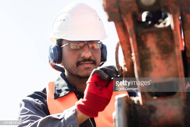 male engineer wearing hardhat and ear protectors working on construction site. - sigrid gombert stock pictures, royalty-free photos & images