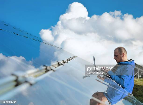 male engineer with laptop working on solar panels - sustainability stock pictures, royalty-free photos & images