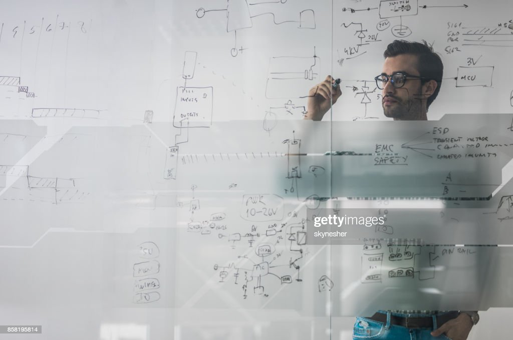 Male engineer working on new ideas and writing diagram on glass wall. : Stock Photo