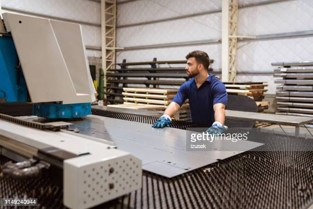 male engineer working on puller machine in factory - focus on foreground stock pictures, royalty-free photos & images