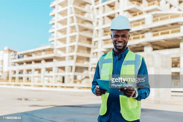 male  engineers in protective helmet and reflective clothing, standing on construction site infront of a large building. - civil engineering stock pictures, royalty-free photos & images