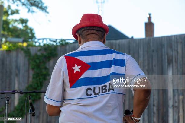 A male entertainer wearing a shirt with a Cuban flag and dancing on stage during the Salsa on St Clair Festival
