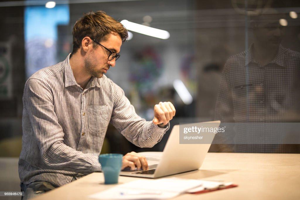 Masculino empreendedor verificar o tempo enquanto estiver trabalhando no laptop no escritório. : Foto de stock