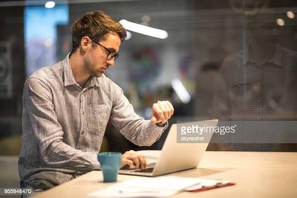 masculino empreendedor verificar o tempo enquanto estiver trabalhando no laptop no escritório. - ver a hora - fotografias e filmes do acervo