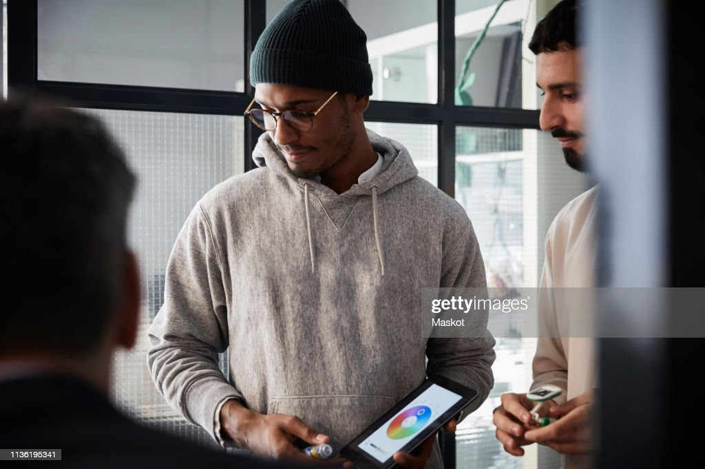 Male entrepreneur holding digital tablet while standing by colleague during meeting in creative office : Stock-Foto