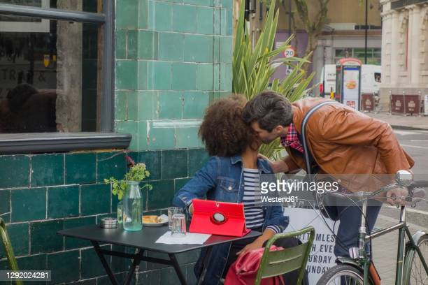 male entrepreneur kissing female colleague at cafe - 30 39 years stock pictures, royalty-free photos & images