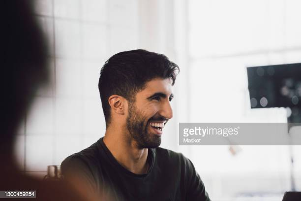 male entrepreneur laughing while discussing in meeting at it startup company - incidental people stock pictures, royalty-free photos & images