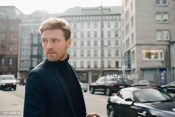 male entrepreneur looking away while standing against building in city - fokus auf den vordergrund stock-fotos und bilder