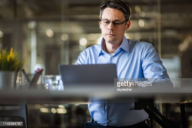 male entrepreneur reading an e-mail on laptop in the office. - businesswear stock pictures, royalty-free photos & images