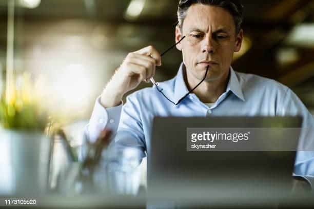 männlicher unternehmer liest eine e-mail auf laptop im büro. - bildungseinrichtung stock-fotos und bilder