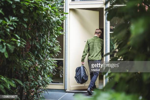 male entrepreneur with bag entering in house - entrare foto e immagini stock