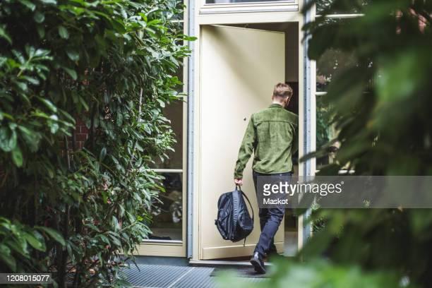 male entrepreneur with bag entering in house - entrar imagens e fotografias de stock