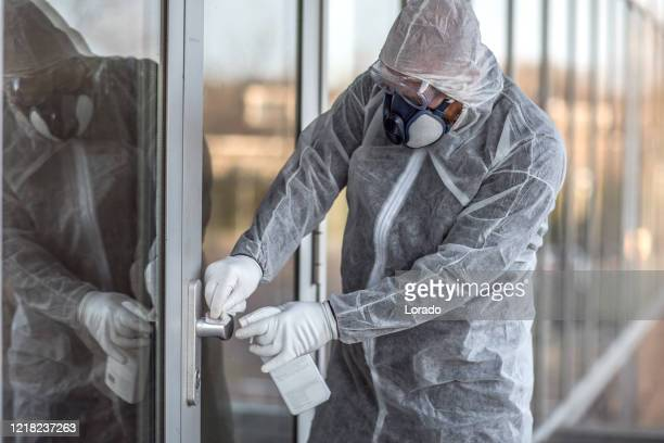 a male essential worker wearing a face mask during virus outbreak - disinfection stock pictures, royalty-free photos & images