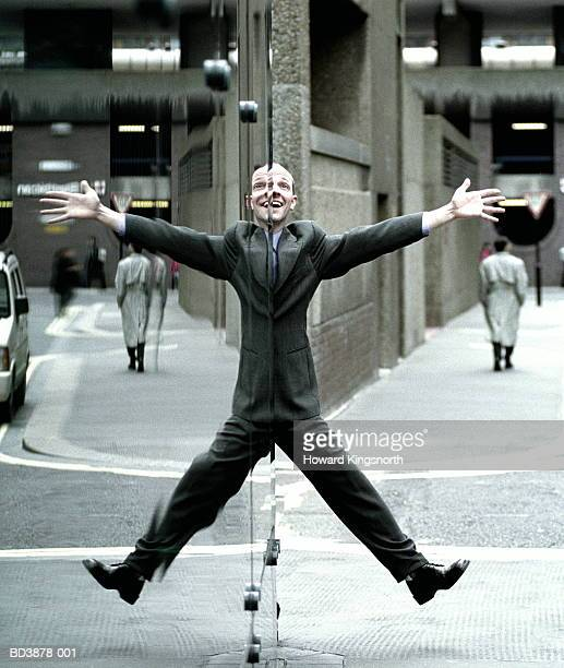 male executive doing star jump, reflection in window - symmetry stock pictures, royalty-free photos & images