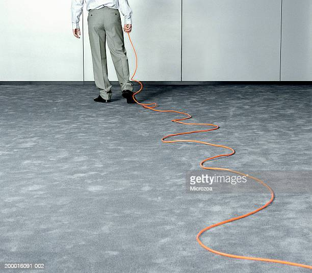male executive dragging extension cable across office, low section - microzoa fotografías e imágenes de stock