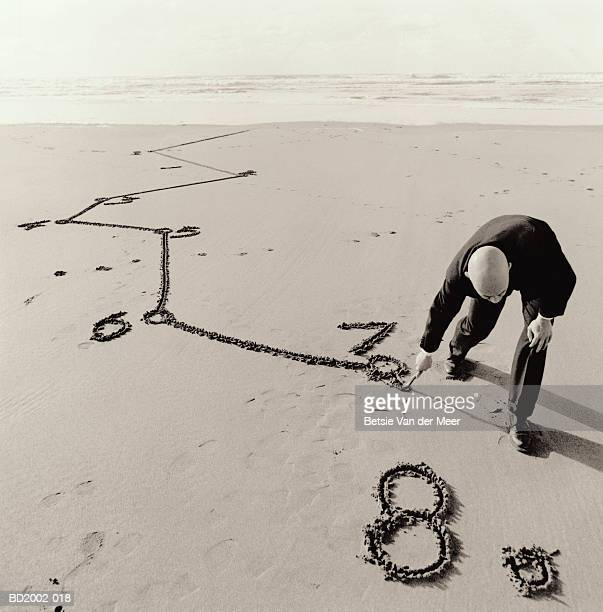 Male executive drawing line between numbers drawn in sand (toned B&W)