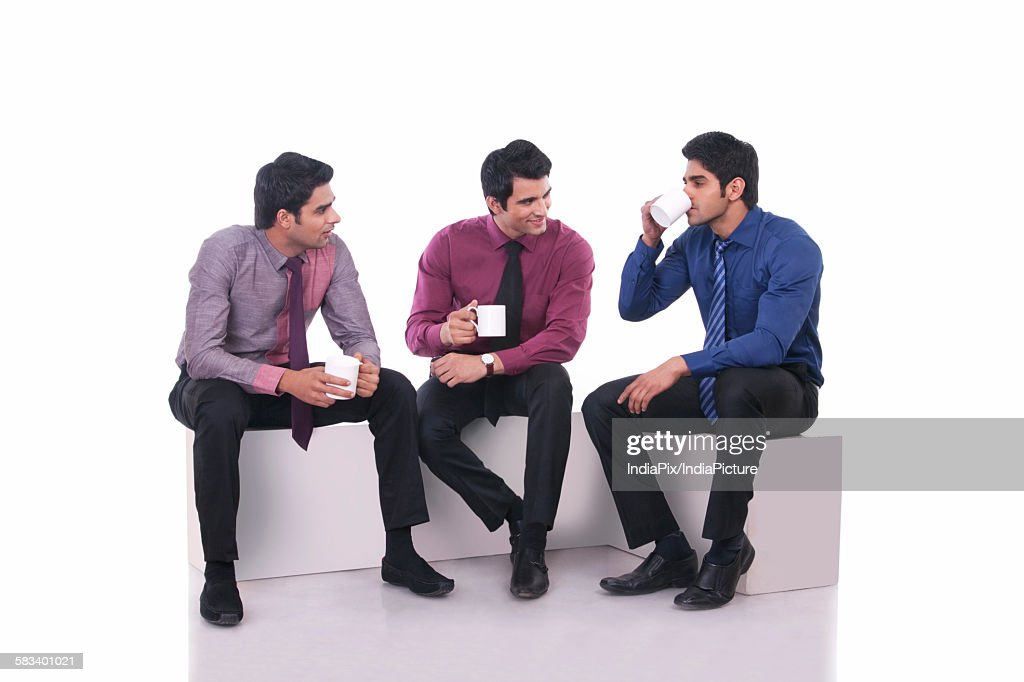 Male executive drinking tea as colleagues watch on : Stock Photo