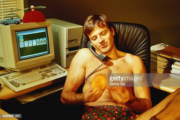 Male executive in underwear sitting at desk using phone