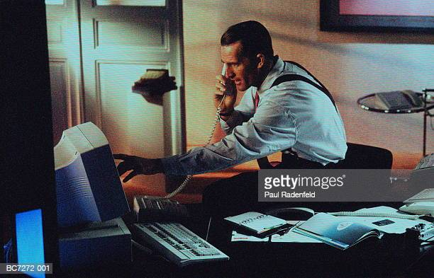Male executive on phone, pointing to computer screen (textured)