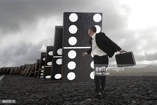 Male executive running from giant falling dominoes