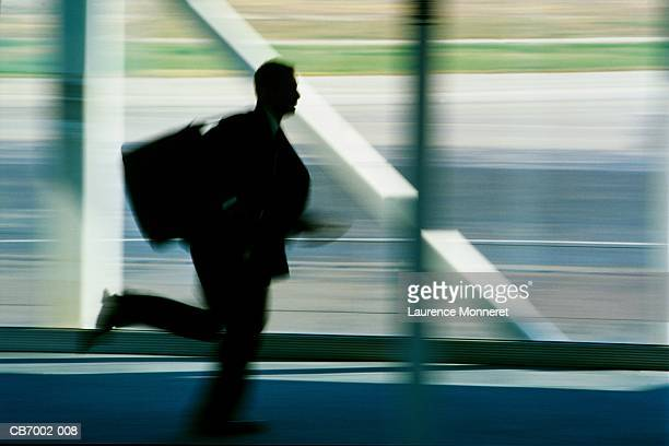Male executive running in airport (blurred motion)