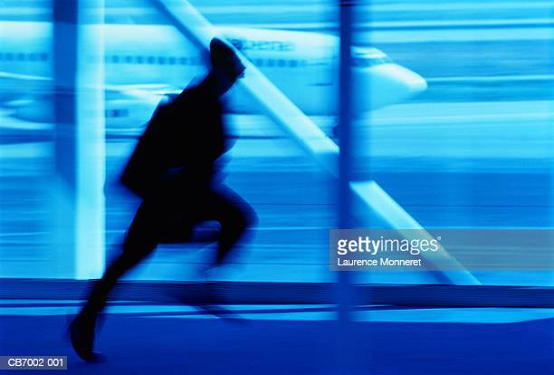Male executive running in airport, silhouette (blurred motion)