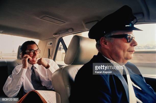 Male executive sitting in  chauffeur driven car (Enhancement)