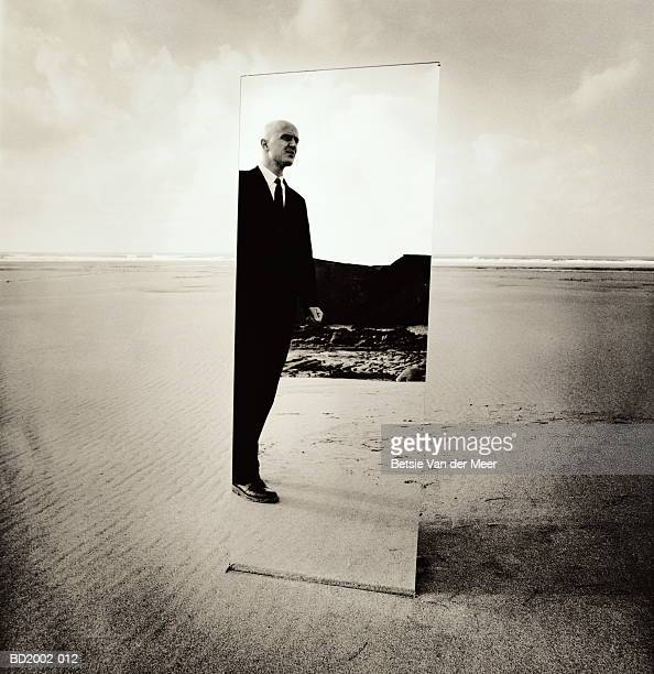 male executive standing on beach, reflection in mirror (toned b&w) - full length mirror stock photos and pictures