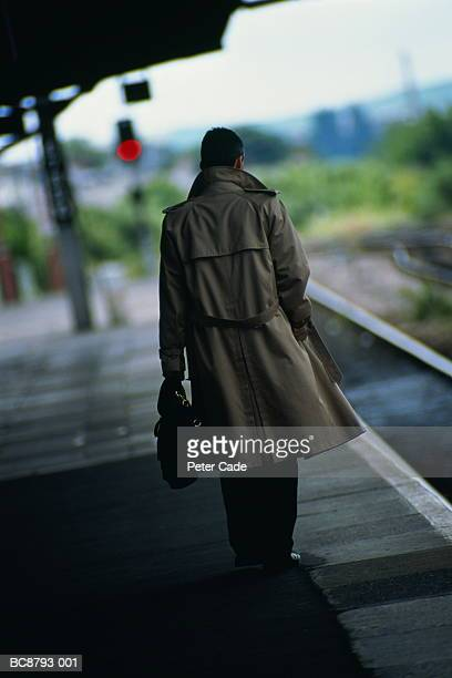 male executive standing on railway station platform, rear view - casacca foto e immagini stock