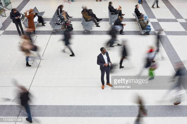male executive standing out from the crowd in train station - uncertainty stock pictures, royalty-free photos & images